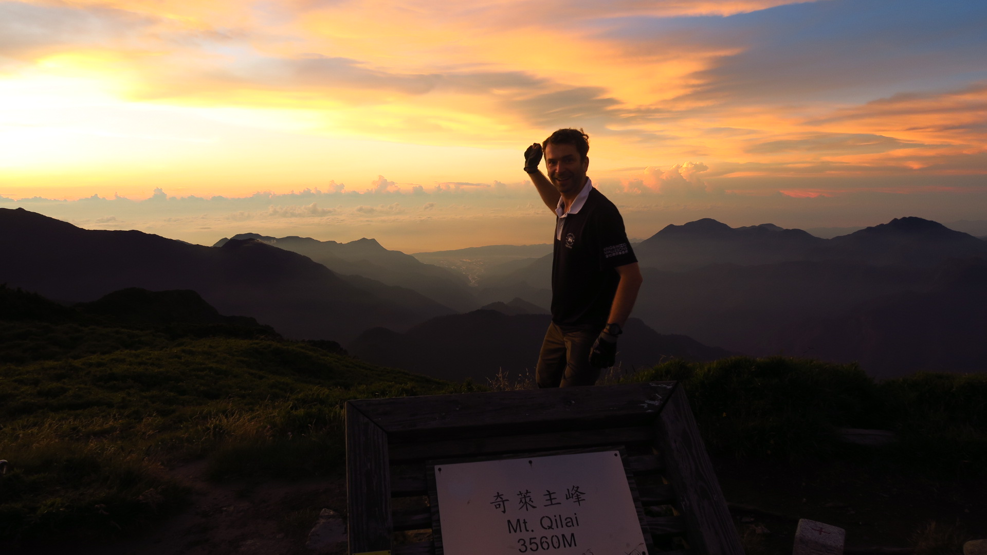 Krzysztof Kostienko at Sunrise at 5:30 AM on Mt. Qulai Taiwan. KK is practicing squash swing after 2 hours hike.   Last year a biker, this year a hiker; lost the bike but are they the same gloves ??